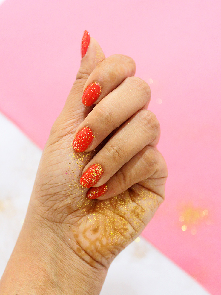 glitter manicure with red nail paint